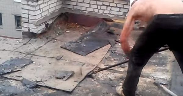 Старое покрытие, предварительно разрезанное на квадраты болгаркой, поддевают ломом и снимают