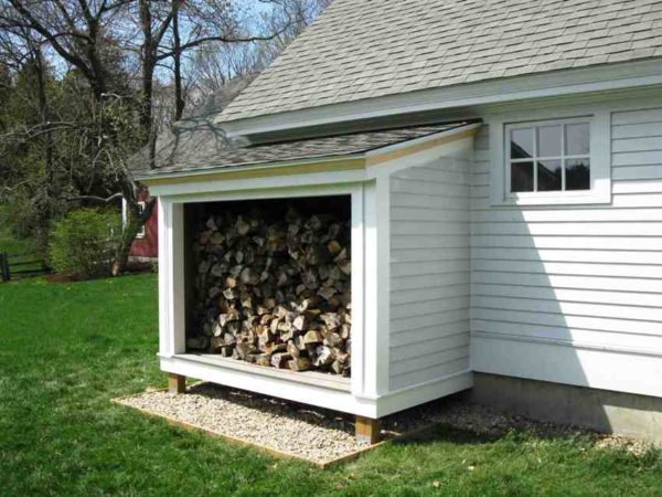 Чтобы пристенный дровник не портил внешний вид дома, для его отделки стоит выбирать те же материалы, которыми отделан фасад